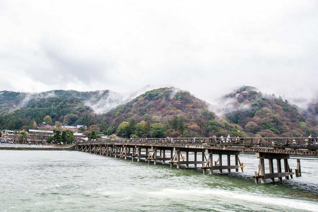 clouds rolling across storm mountain Arashiyama beyond Togetsu-kyo Bridge
