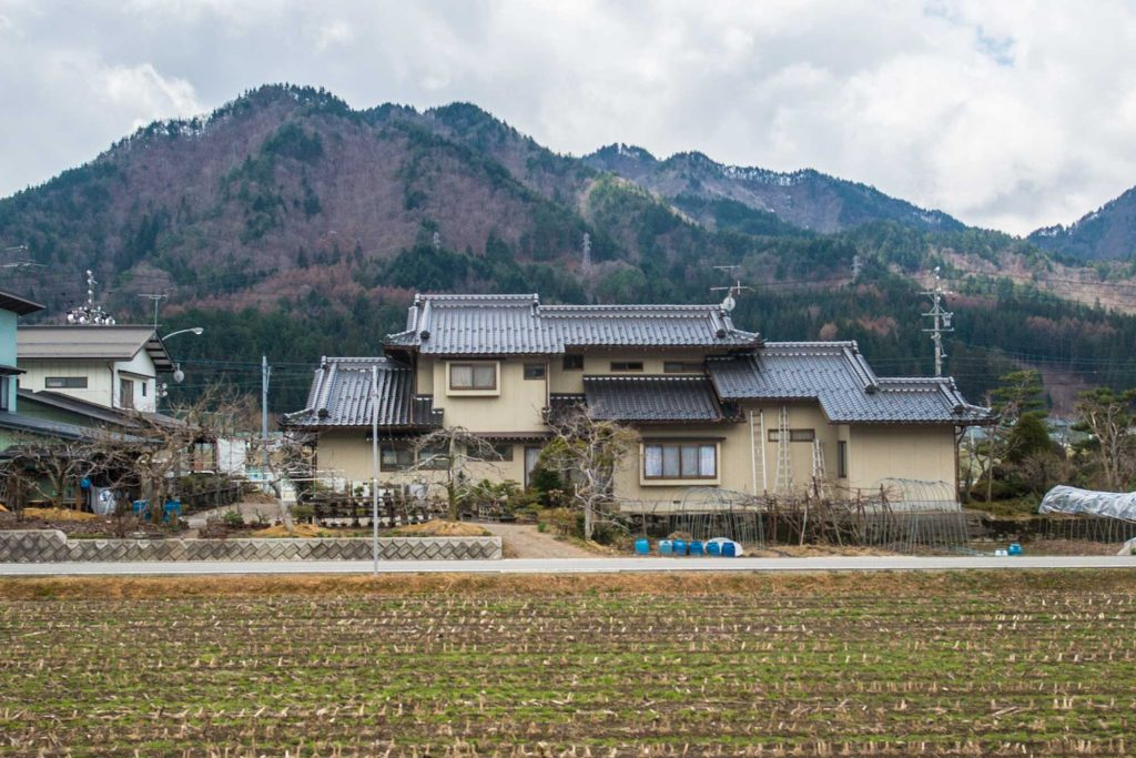A large rural house between Takayama and Kanazawa against a mountain in Japan