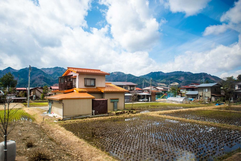 A small house with a rice paddy in the back yard in japan's mountains